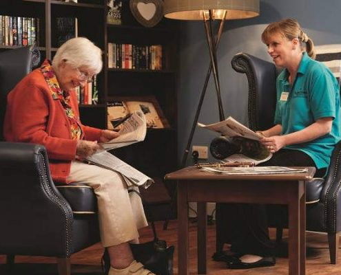A resident & staff in the library